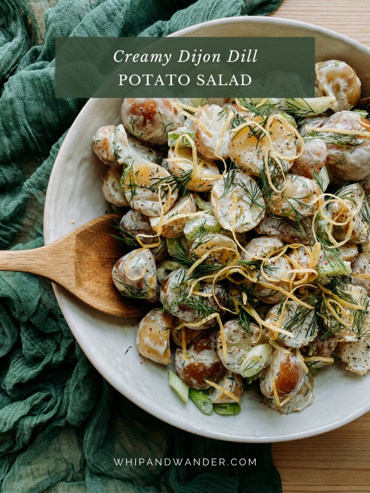 a wooden serving spoon dipping into a bowl of potato salad in a white bowl on a green cloth