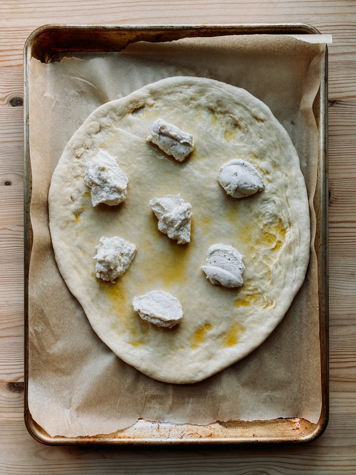 dollops of ricotta cheese on top of a pizza dough