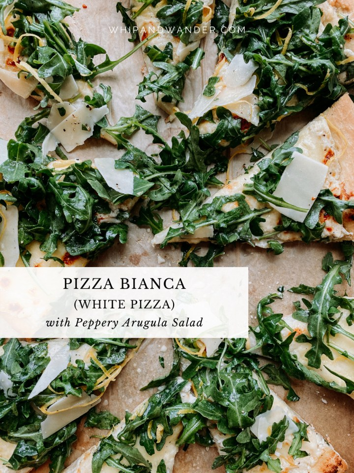 slices of white pizza on a baking sheet with arugula salad on top