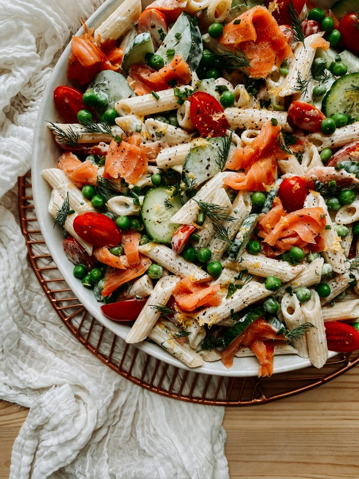 a white bowl with smoked salmon pasta salad resting on a brass tray with a white cloth underneath