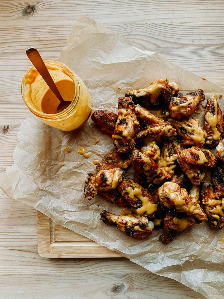 a glass jar of carolina gold bbq sauce resting ona. cutting board with chicken wings