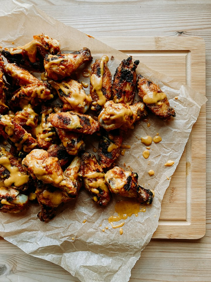 a pile of grilled chicken wings on a parchment lines cutting board