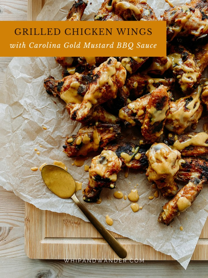a pile of grilled chicken wings with gold sauce on a parchment lined board