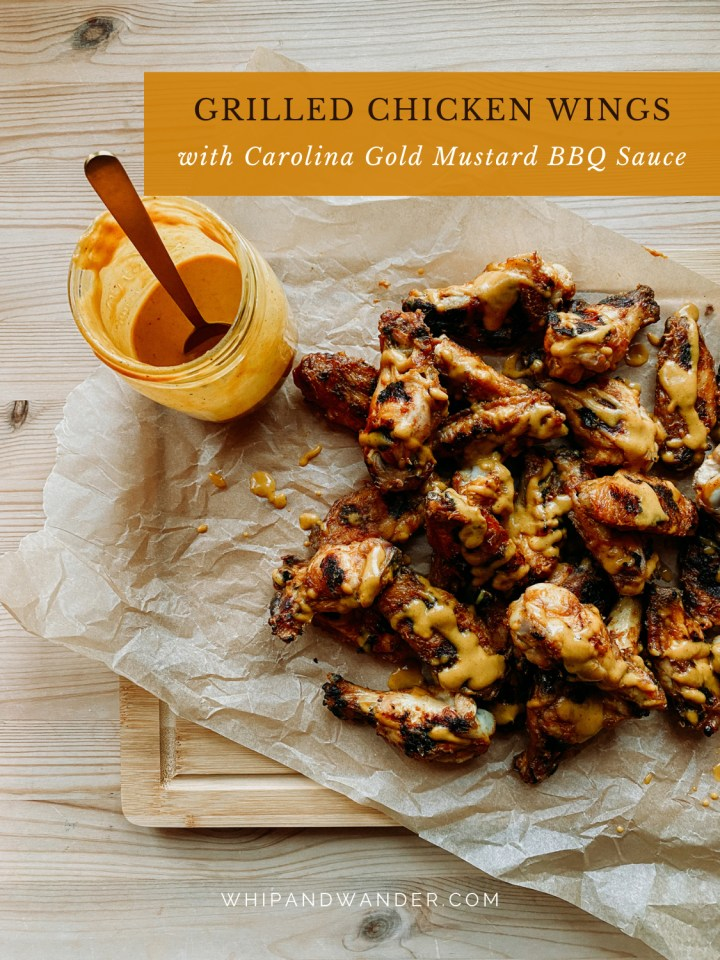 a jar of carolina gold bbq sauce next to a pile of grilled chicken wings on a wooden board
