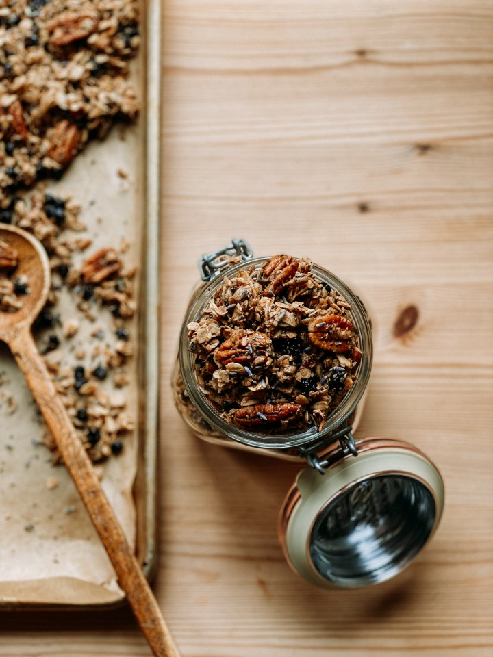 a glass jar filled with Honey Lavender Blueberry Granola next to a baking tray with more of the granola resting on a wooden table