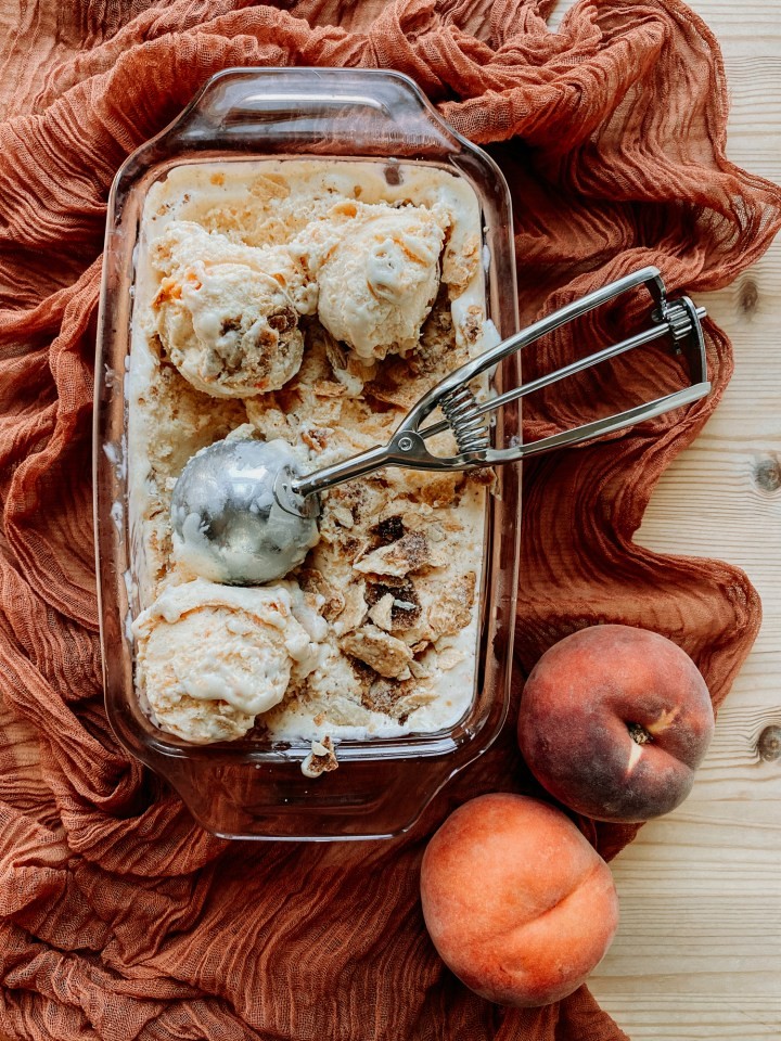 Buttermilk Peach Pie Ice Cream in a glass pan resting on a cloth with two fresh peaches nearby