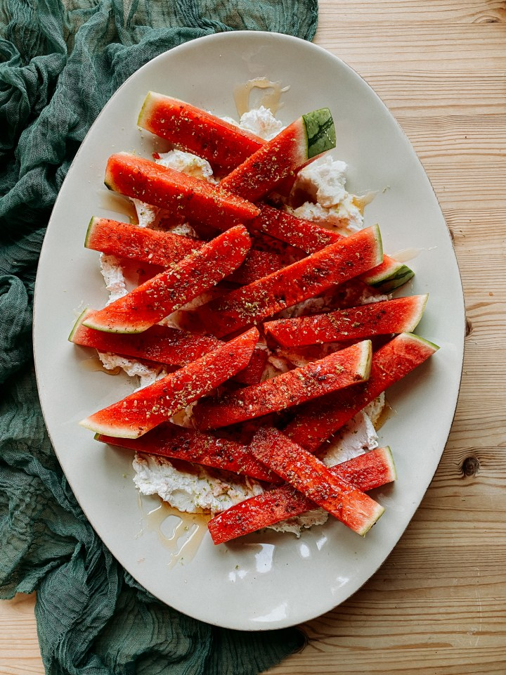 Chili Lime Watermelon with Labneh and Honey on a large white platter on a green cloth lined wooden table
