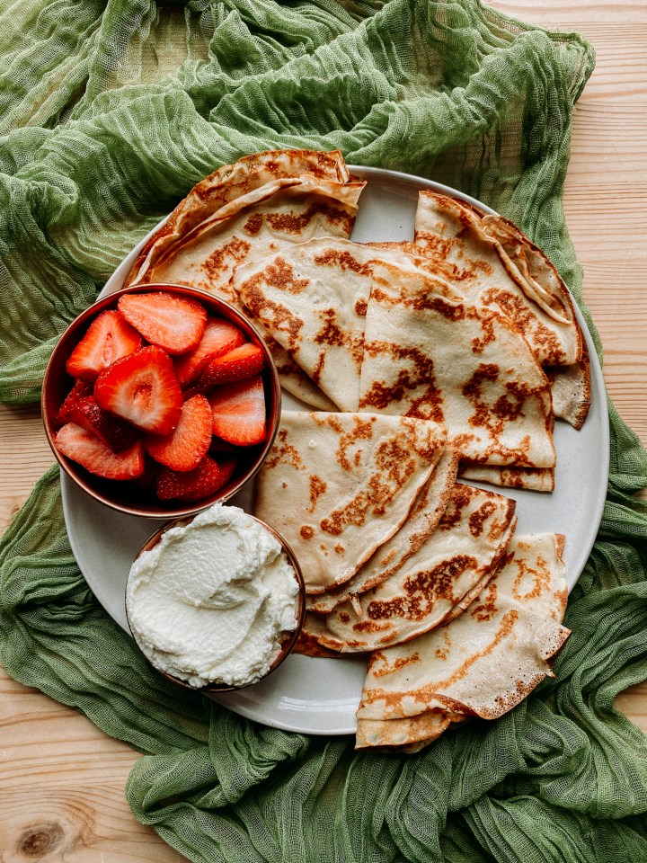Classic French Crepes on a plate with fresh whipped cream and a bowl of strawberries