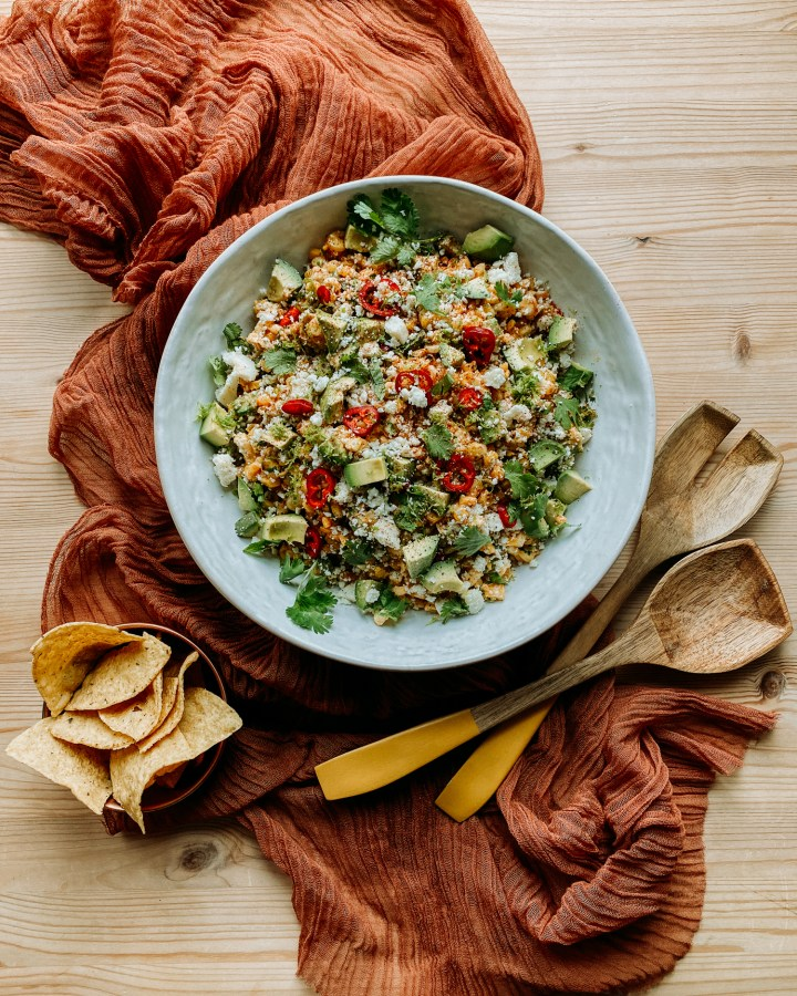 Grilled Corn Salad with Spicy Honey Lime Dressing in a large white serving bowl on a rust colored cloth with a bowl of tortilla chips and wooden salad servers resting nearby