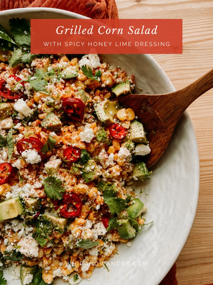 a wooden serving spoon resting in a bowl of Grilled Corn Salad with Spicy Honey Lime Dressing