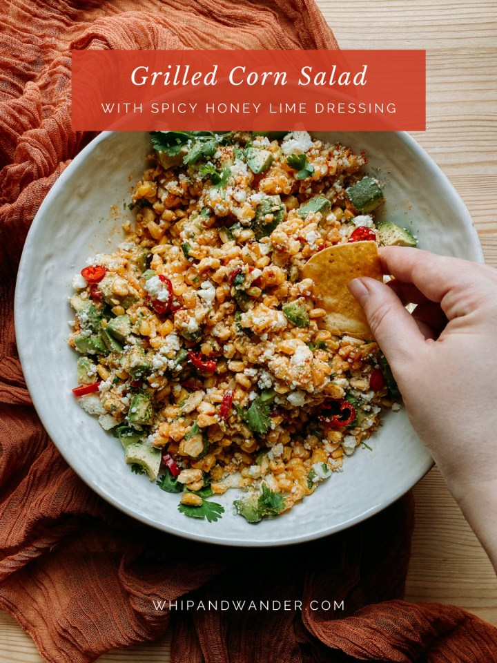 a hand using a tortilla chips to scoop corn salad with honey lime dressing up