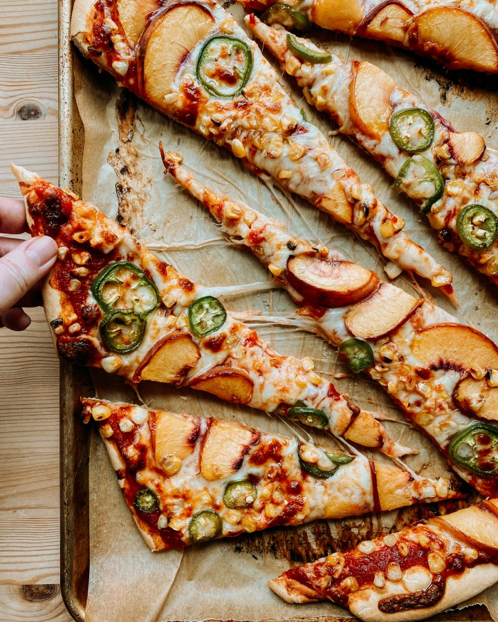 a hand grabbing a slice of Peach, Corn, and Jalapeno Pizza with Honey off of a baking tray