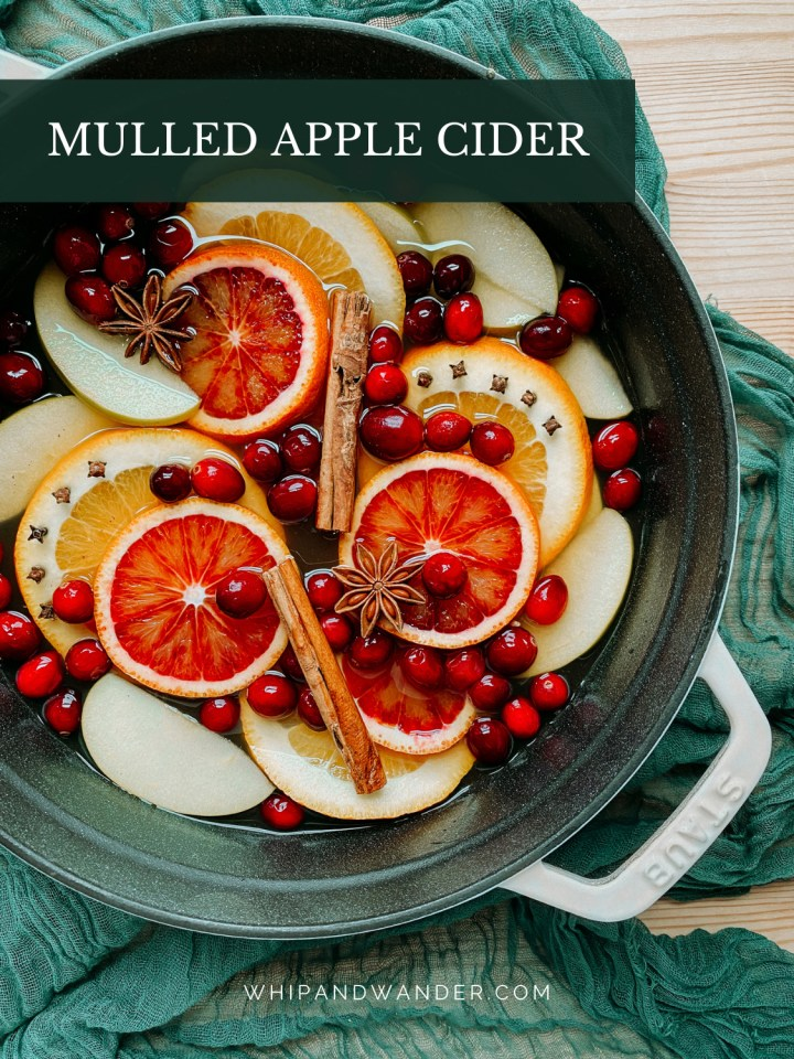 a white dutch oven filled with slices citrus, apples, cranberries, mulling spices, and apple cider