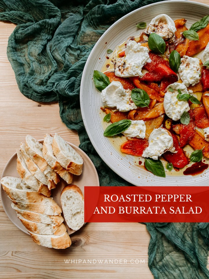 a white platter with Roasted Pepper and Burrata Salad resting ona. dark teal towel next to a plate of sliced bread on a wooden surface
