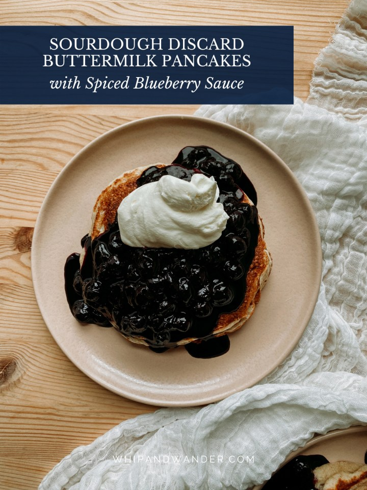 a pink plate with a whipped cream and blueberry sauce topped pancake