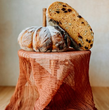 A loaf of Pumpkin Sourdough Bread cut in half and resting on a fabric lined cake stand