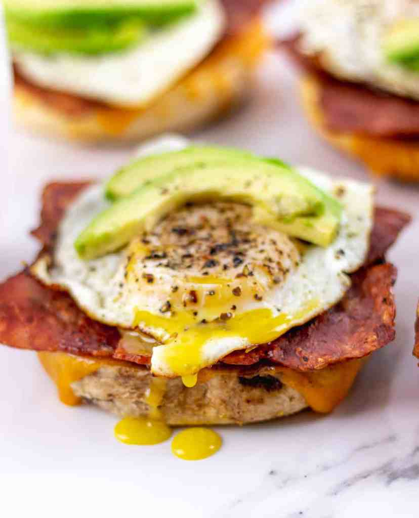 a close up of an avocado breakfast bagel after the fried egg has been popped