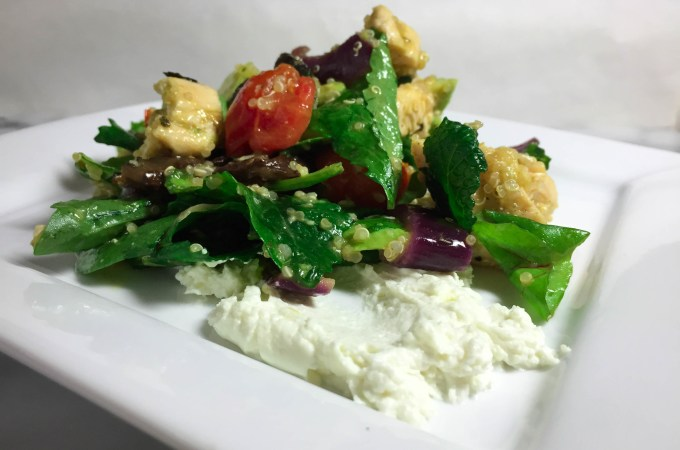 Roasted veggie salad on a plate with goat cheese