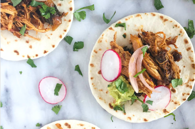 Braised Adobo Chicken Tacos topped with sliced radishes, guacamole, pickled onions and cilantro