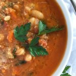 A bowl of white bean tomato soup topped with parmesan, bread crumbs and parsley from the top