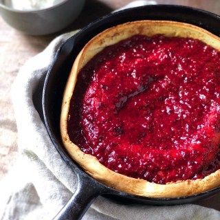 Brambleberry Lavender Dutch Baby in a cast iron pan next to a bowl of lavender whipped cream