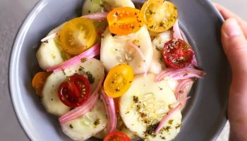 Marinated cucumber tomato salad being held up on a plate
