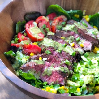 A wooden salad bowl of flat iron steak salad with chimichurri vinaigrette