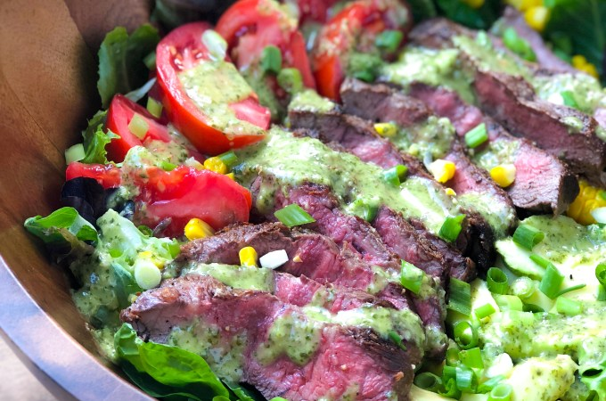 A wooden salad bowl of flat iron steak salad with chimichurri vinaigrette