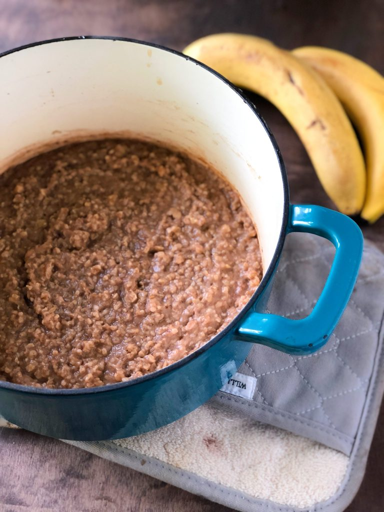 A blue dutch oven filled with banana nut steel-cut oatmeal on a pot holder with banans in the background.