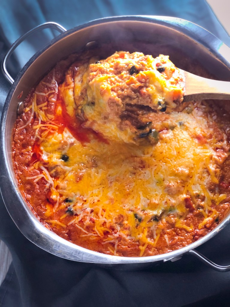 Cheesy Vegetarian Quinoa Enchilada Bake in a metal pot, with a wooden spoon taking a scoop with stretchy cheese.