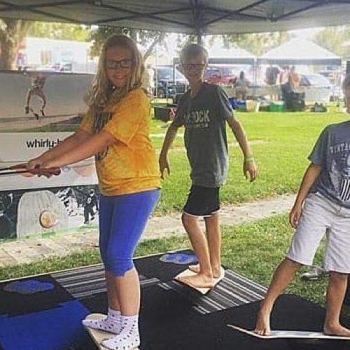 Three kids using their whirly boards at the farmers market