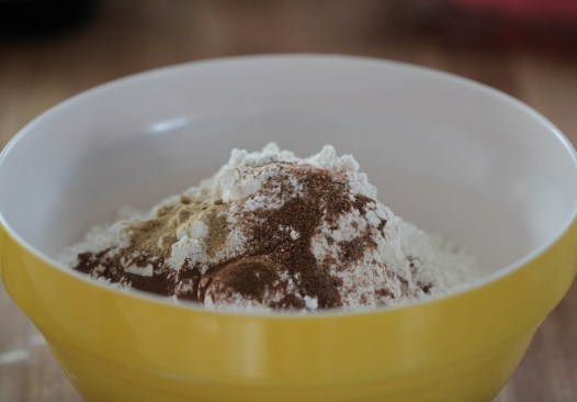 Flour, sugar, and spices sit piled in a yellow bowl.