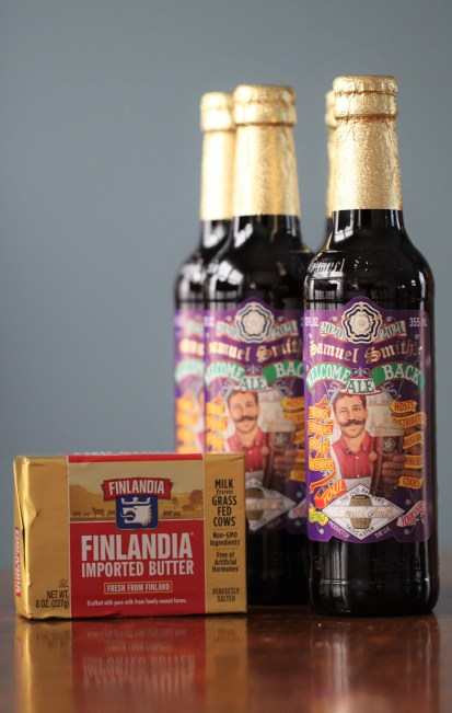 Several bottles of Samuel Smith's Winter Warmer Ale (Welcome Back Ale, 2020-2021 edition) sit on a wooden surface next to an unopened package of Finlandia butter.