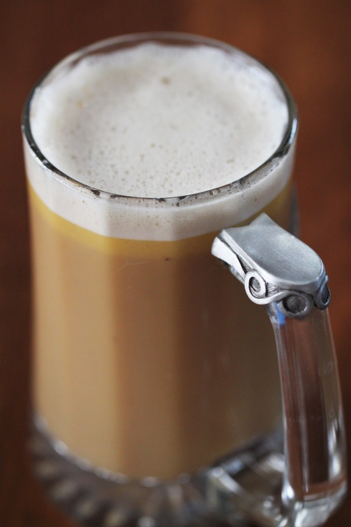 A clear mug is filled with golden butterbeer, topped with a small head of white foam.