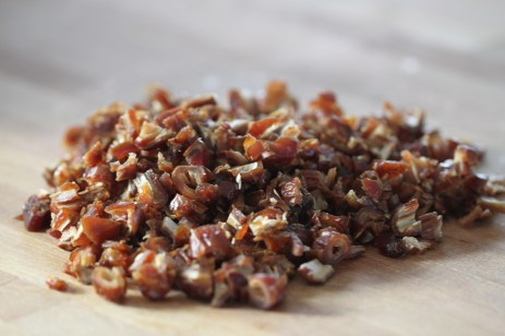 A pile of chopped dates sits on a wooden surface.