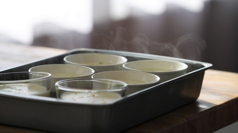 Six ramekins and two pyrex bowls, all filled with the cream mixture, sit in a 9 by 13 baking dish. A few wisps of steam are just visible wafting up above the baking dish.