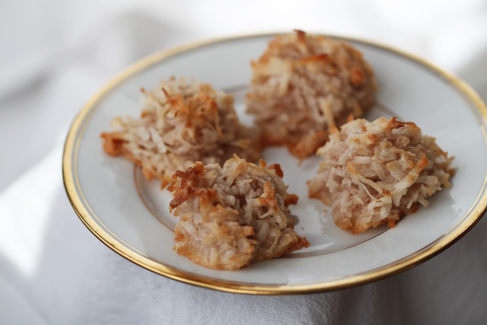 Four coconut macaroons sit on a gold-rimmed white china plate. The macaroons are essentially toasted coconut haystack cookies, with cream-colored centers and toasted edges.