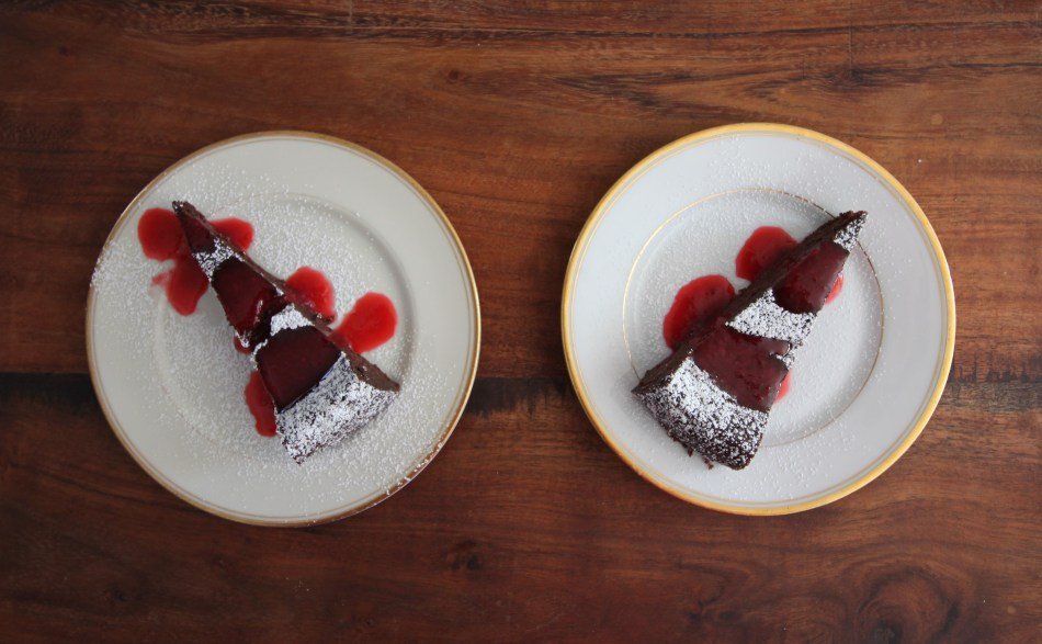 Two slices of chocolate truffle torte sit atop gold-rimmed china plates. Each brown slice of torte is dusted with powdered sugar and drizzled with bright red raspberry sauce.