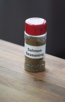 """A full plastic spice container with a homemade label reading """"Salmon Seasoning"""" sits on a wooden surface."""