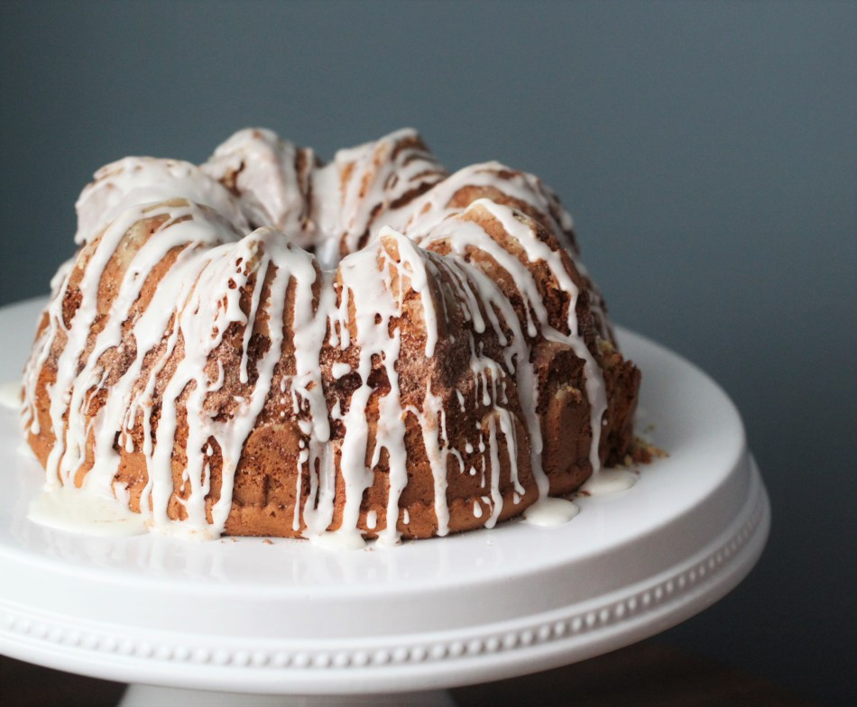 A coffee cake has been baked in a bundt pan and drizzled with white icing. It sits on a white pedestal against a blue background.