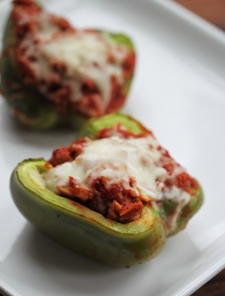 Two stuffed peppers - green bell peppers, stuffed with ground turkey and topped with tomato sauce and melted cheese - rest on a white plate.