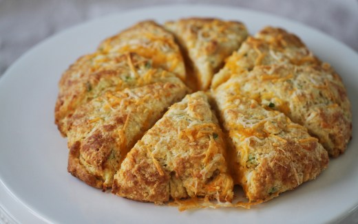 Cheese and onion scones sit, sliced, on a white plate.