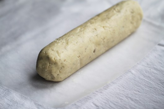 The dough has been rolled into a log and sits atop a piece of cut wax paper on a white cloth surface.