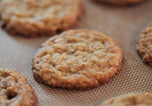 Baked oatmeal cookies sit on a silicone mat.