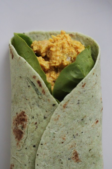 Vegan coronation chicken is a yellow salad made from mashed chickpeas . It rests inside a set of spinach leaves, folded within a green tortilla, which sits on a white surface.