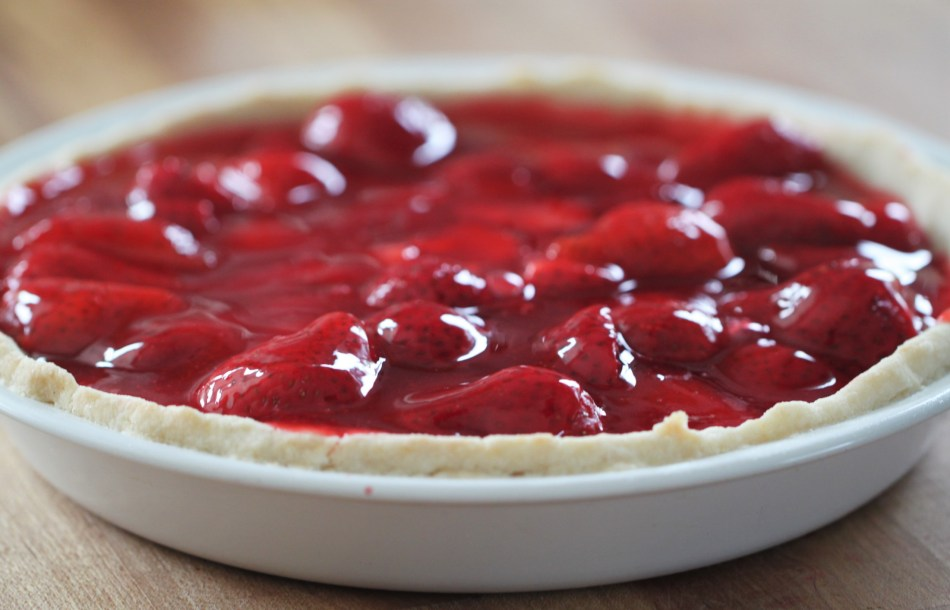 A gluten free strawberry pie sits in a white pie plate on a wooden countertop. This strawberry pie recipe can be gluten free, or it can be made with a traditional pie crust.