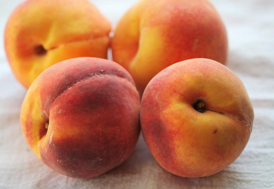 Four fresh, bright orange peaches sit on a white cloth surface.