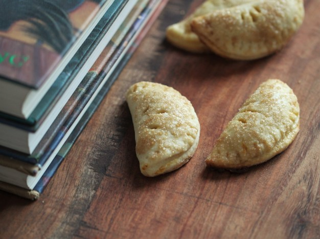 Several pumpkin pasties sit on a wooden surface next to a stack of Harry Potter books.