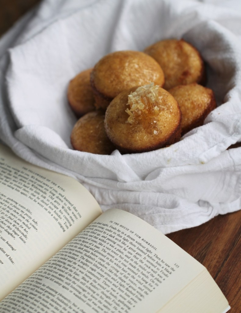 Six of Beorn's honey cakes sit in a bowl that is wrapped in a white towel. The honey cakes are golden in color, and one is topped with a piece of honeycomb.
