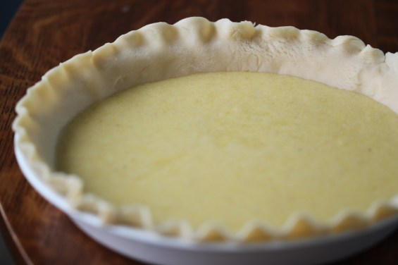 A prepared (storebought) pie crust sits on a wooden surface, filled with chess pie filling. The pie is unbaked in this photo and both the crust and the filling are quite pale.